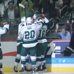Featured Image Caption:Iowa Wild forward Brett Bulmer is mobbed by teamamtes Brian Connelly, Chad Rau and Jason Zucker after Bulmer scored the Wild's first-ever goal, Saturday, Oct. 12, 2013, in Des Moines, Iowa. The 1-0 win was the AHL franchise's first in its new Iowa home. (Iowa Wild Photo by Reese Strickland)
