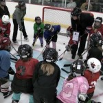 Featured Image: Alexandria's rink rookies huddle for a quick chat. The association's intro-to-hockey offerings have generated unprecedented local interest. (Photo by Joe Korkowski)