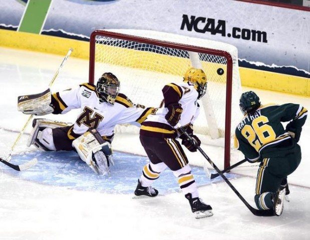 Clarkson University's Jamie Lee Rattray (26) blasts a goal past University of Minnesota goalie Amanda Leveille, left, as Dani Cameranesi (21, center) defends during the 2nd period of the Women's NCAA Ice Hockey Championship held at the TD Bank Sports Center in Hamden, CT. Clarkson defeated Minnesota 5-4 for the school's first national title. (Credit: Sean Elliot | NCAA Photos)