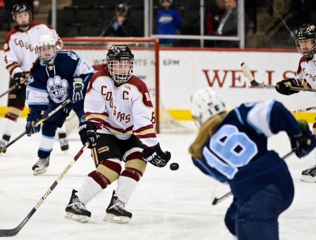 Blaine's Sam Auman fires a shot toward the Lakeville North net as the Cougars' Kelsey Olsen defends. (MHM Photo / Tim Kolehmainen)