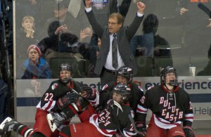 Duluth East coach Mike Randolph raises his arms in jubilation after the Greyhounds' stunning upset of Edina 3-1 in the Class 2A semifinals on Friday night at Xcel Energy Center. (Photo / Tim Kolehmainen - Breakdown Sports USA)