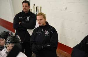 New Hamline University women's coach Natalie Darwitz keeps an eye on her team in the Pipers' 2015-16 home opener vs. UW-River Falls on Nov. 6, 2015 at St. Paul's Oscar Johnson Arena. (Photo credit: Cole Meyer, Hamline)